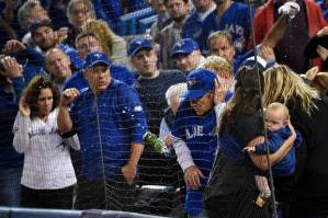 Blue Jays fans duck in fear of being hit by beer and trash during the 7th inning of Game 5 of the Texas Rangers-Toronto Blue Jays game.